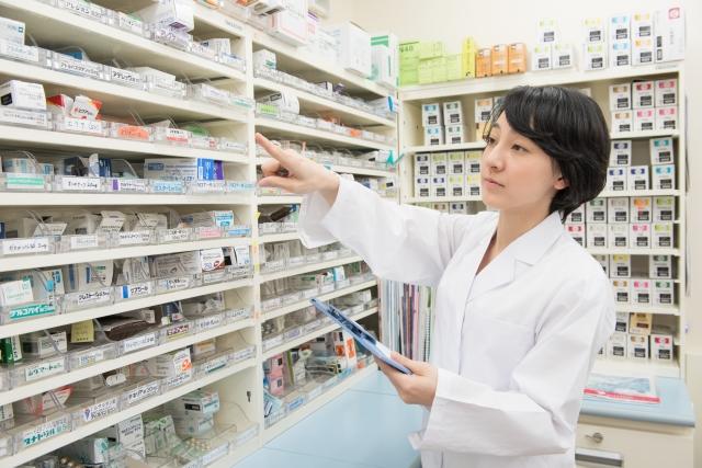棚の薬を選ぶ女性薬剤師3