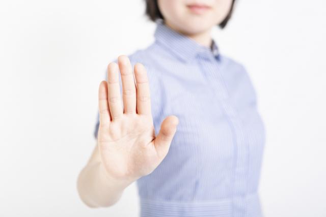 拒否のハンドサインをするワンピースを着た女性