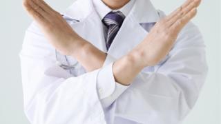 禁止のポーズをとる男性薬剤師