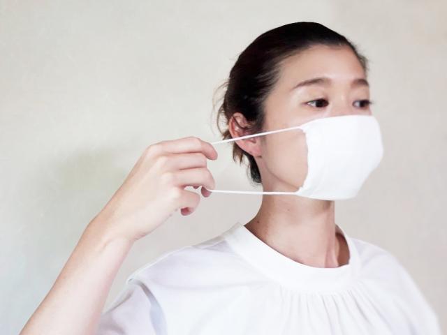 マスクの紐を伸ばす女性