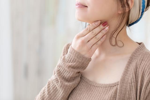 喉を触る女性